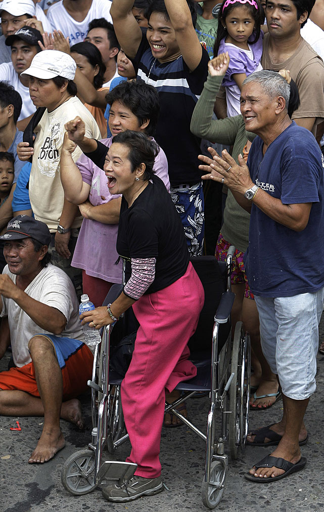 Yolanda Dominguez, 59, stands on her wheelchair and cheers while watching the live satellite broadcast of the fight.