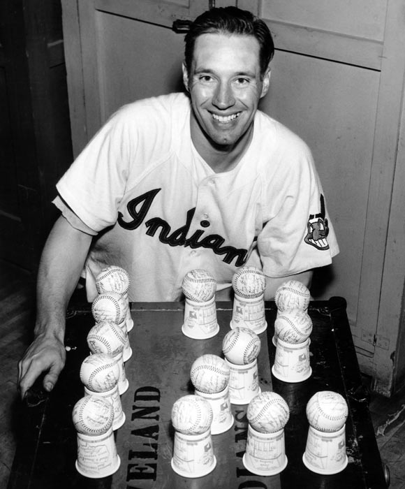 Feller  poses with 12 baseballs after his 12th victory of the 1954 season. Overall, Feller spent 18 seasons in Cleveland with a career record of 266-162 and a 3.25 ERA.