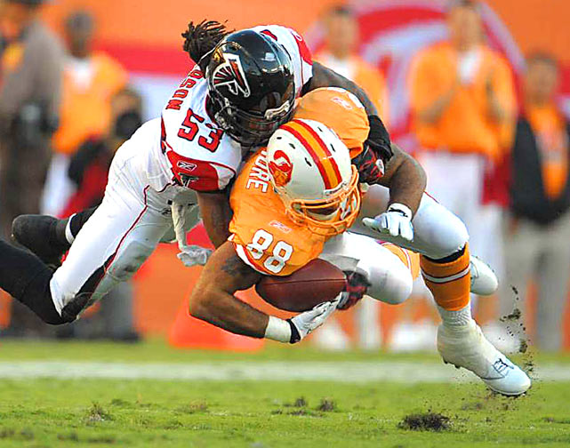 Tight end John Gilmore of the Tampa Bay Buccaneers is tackled by linebacker Mike Peterson of the Falcons during their game December 5 at Raymond James Stadium in Tampa. Atlanta defeated Tampa Bay 28-24.