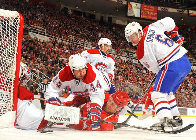 Canadiens defenseman Roman Hamrlik (44) falls on top of Red Wings forward Danny Cleary in front of the net of goalie Carey Price during their game Dec. 10 at Joe Louis Arena in Detroit. The Red Wings won 4-2.