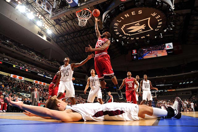 Texas A&M forward Nathan Walkup (bottom) lies helpless on the floor as Arkansas Razorback forward Marshawn Powell drives to the hoop during their game at the American Airlines Center in Dallas, Texas. Texas A&M beat Arkansas 71-62.