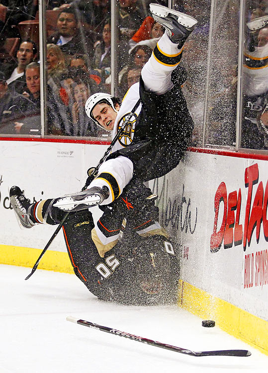 Boston Bruins defenseman Adam McQuaid has his feet cut out from under him by Anaheim Ducks rightwinger Troy Bodie in the second period of a Bruins-Ducks game.