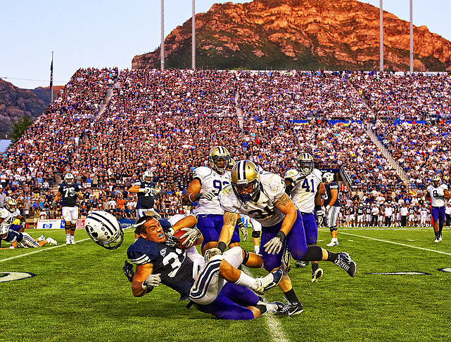 BYU Cougars running back Bryan Kariya (left) loses his helmet as Washington Huskies linebacker Cort Dennison and another Huskies defender pull him to the ground.  With the Wasatch Mountains providing the backdrop, the Cougars would defeat the Huskies 23-17.