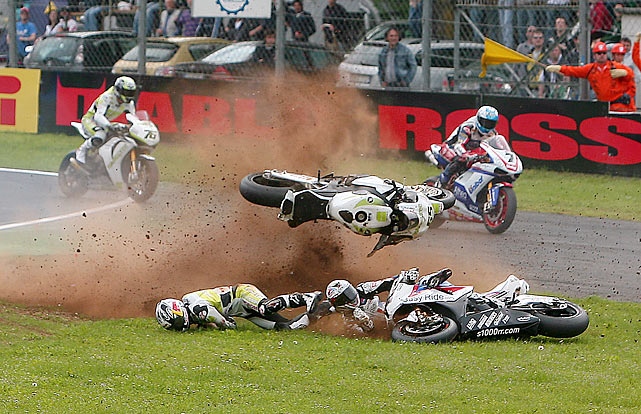 Two riders lay low after while a motorcycle is airborne during the Monza Superbike world championship in Monza, Italy.  The race was the fifth round of the Superbike world championship season.