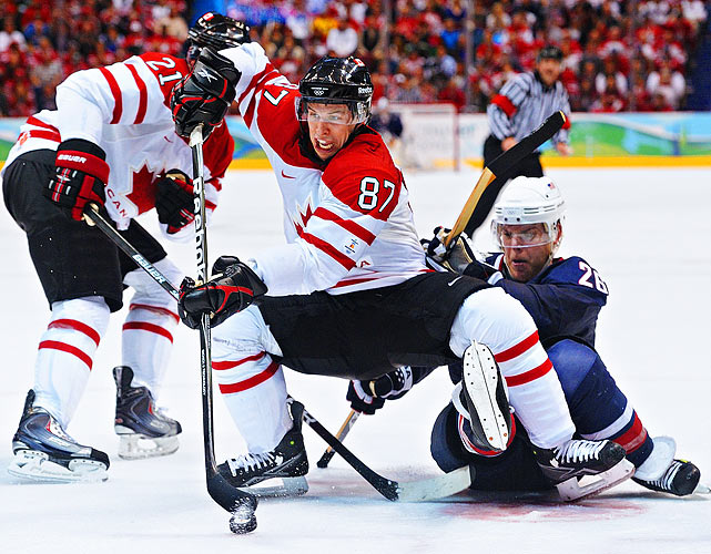 Sidney Crosby (87) of Canada jockeys for position with U.S. hockey player Paul Stastny during the gold medal game at the Winter Olympics.  Crosby would score the winning goal in overtime as Canada defeated the U.S. 3-2.