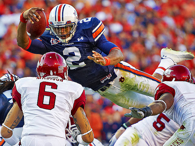 Auburn quarterback Cam Newton dives over Arkansas Razorbacks defenders for a touchdown during a 65-43 victory at Jordan-Hare Stadium in Auburn, Ala. Newton would score three touchdowns during the game.