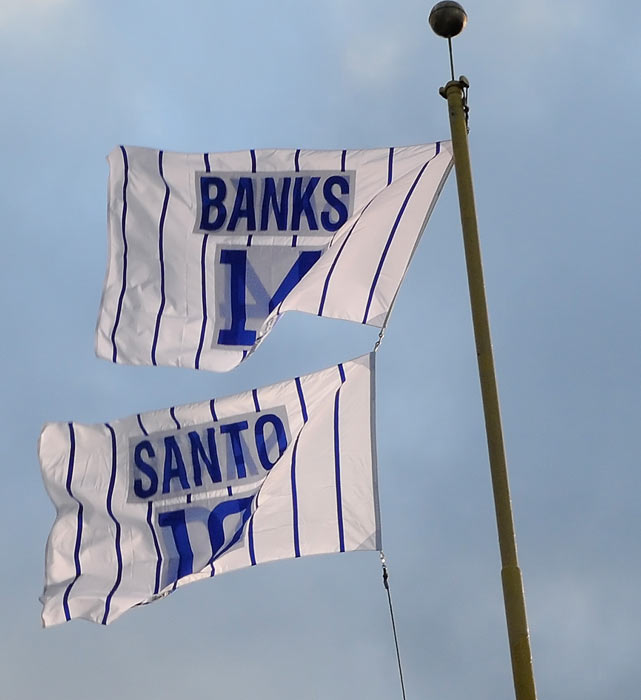 Ernie Banks and Ron Santo flags fly in the right field corner of Wrigley Field. Santo is one of seven Cubs to have his number retired at Wrigley, joining Banks, Ryne Sandberg, Billy Williams, Greg Maddux, Ferguson Jenkins and Jackie Robinson (whose number is retired throughout baseball).