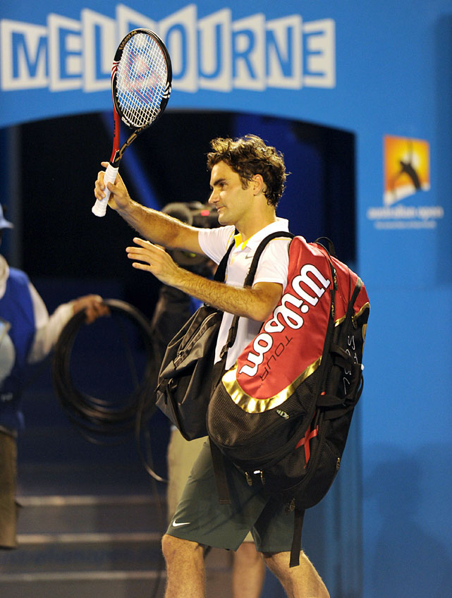Federer waves as he leaves the court.