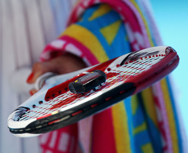 Wozniacki checks her racket strings during a changeover.