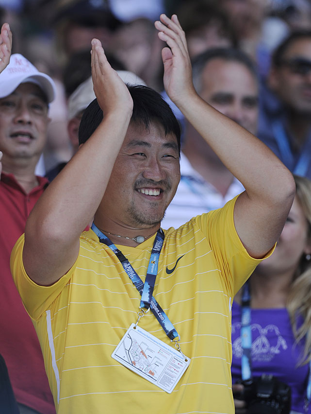 Jiang Shan, coach and husband of Li Na, applauds his wife as she speaks to the crowd following her win over Wozniacki.