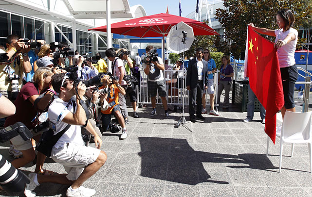 Li holds up her national flag for photographers at the Australian Open.