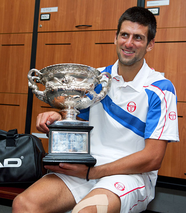 Djokovic sits in the players' locker room with the trophy.