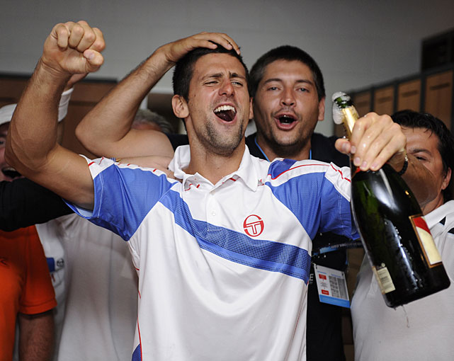 Djokovic celebrates with family and friends in the players' locker room.