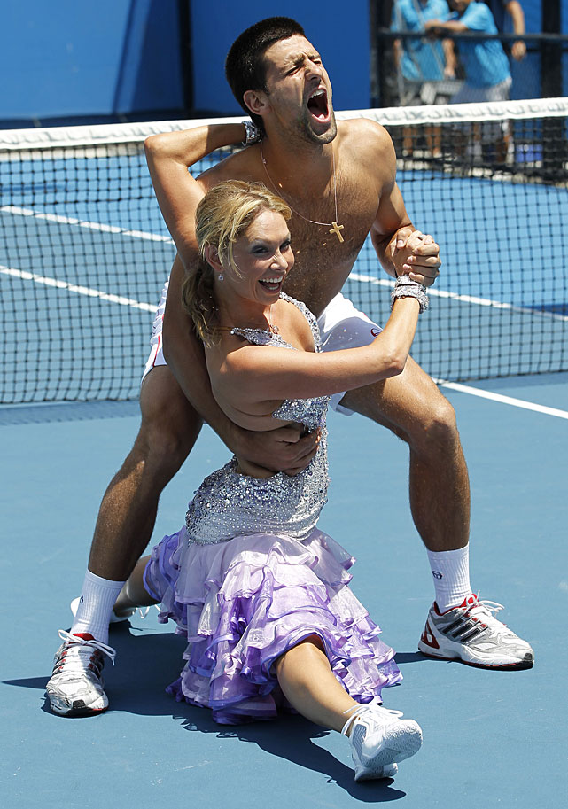 Djokovic grimaces in mock pain as he is given a ballroom dancing lesson on a outer court after his victory over Troicki by Kim Johnson of  Dancing with the Stars .