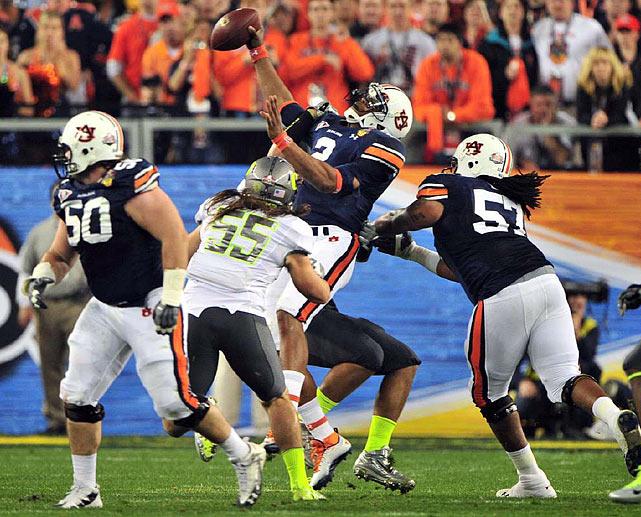 Casey Mathews (55) helps Oregon get one of its two sacks of Auburn quarterback Cam Newton.