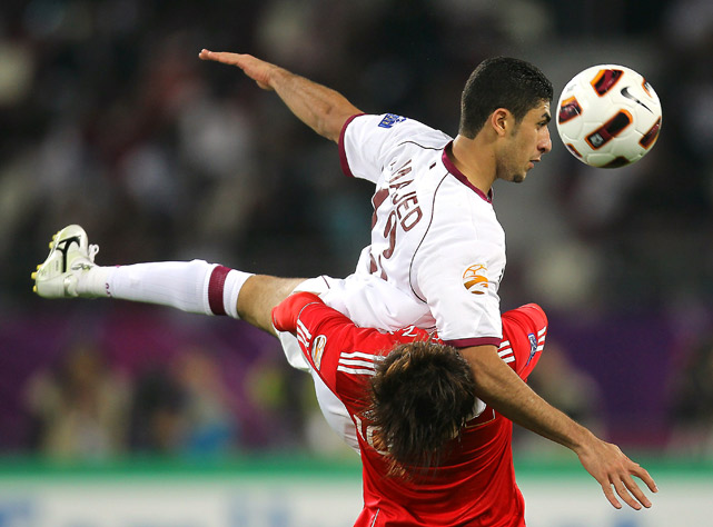 Qatar defender Ibrahim Majed jumps over China midfielder Deng Zhuoxiang to head the ball during their 2011 Asian Cup group A football at Khalifa Stadium on Jan. 12 in Doha.