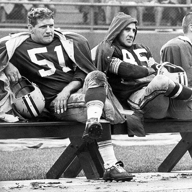 Jim Ringo (51) and Max McGee (85) sit on the bench during a cold game in Green Bay.