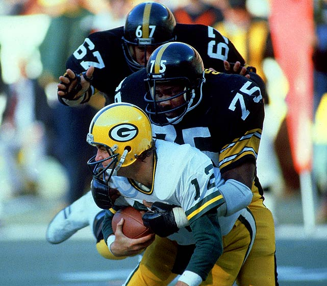 "A staple of the Steel Curtain defense in the 1970's, ""Mean Joe"" Greene sacks Green Bay quarterback Lynn Dickey during a Nov. 2, 1980, game at Three Rivers Stadium. Greene played his entire career with Pittsburgh, recording 78.5 sacks in 13 seasons. He made 10 Pro Bowls and was inducted into the Hall of Fame in 1984."