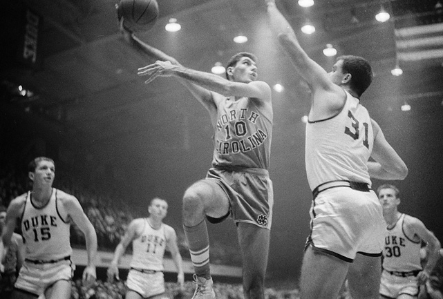 Rosenbluth shoots a sky over hook over a Duke defender. The Tar Heel legend holds the school record for most points (895) and highest scoring average in a single season (28.0).