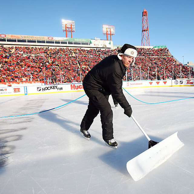 A worker shovels the ice. The puck bounced around the surface early on during the game.