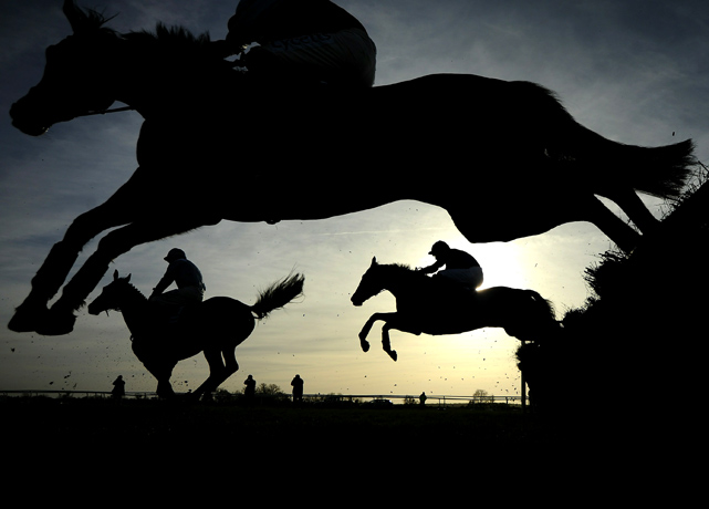 Riders jump over a hurdle at Huntingdon racecourse on Feb. 24 in Ascot, England.