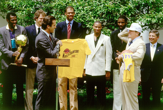 Head coach Pat Riley and the rest of the Los Angeles Lakers visit the White House with a Lakers hat and jersey for President Reagan after winning the NBA title.