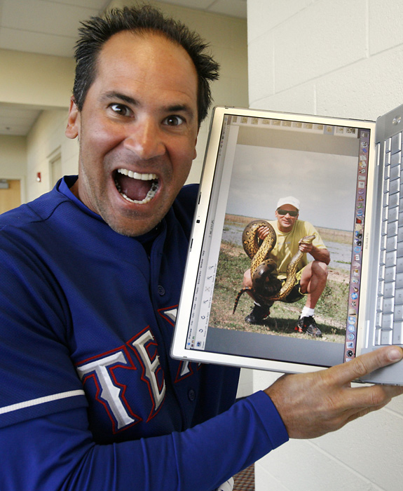 Rangers infielder Omar Vizquel laughs as he shows a photo of himself holding an 11-foot anaconda that he caught during the 2008 offseason.