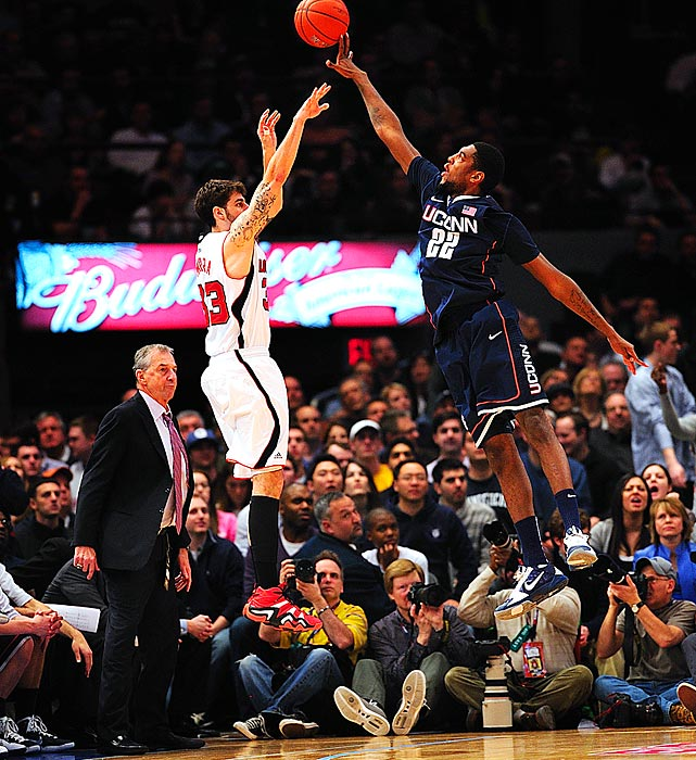 Connecticut Huskies forward Roscoe Smith blocks a three-point attempt from Louisville Cardinals guard Mike Marra during UConn's 69-66 victory in the Big East tournament championship game.