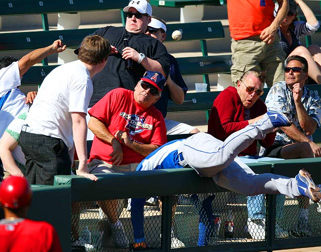 A Kansas City Royals player dives into a petrified crowd for a foul ball during the Royals' 8-2 loss against the Los Angeles Angels of Anaheim in spring training on March 10.
