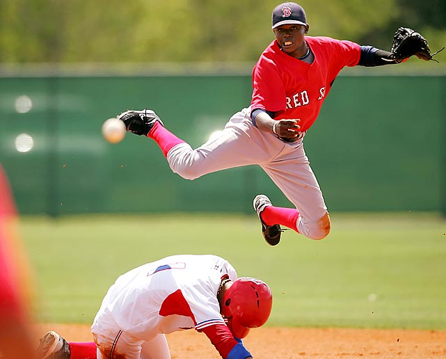 Red Sox prospect Jose Vinicio leaps  to complete the double-play during a game between the Dominican Prospect League team and the Boston Red Sox Rookie League team at the Red Sox Player Development Complex in Ft. Myers, Fla.