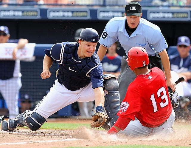 Los Angeles Angels third baseman Macier Izturis (right) safely slips under a  tag from San Diego's Nick Hundley during a spring training game at Peoria Stadium in Arizona.