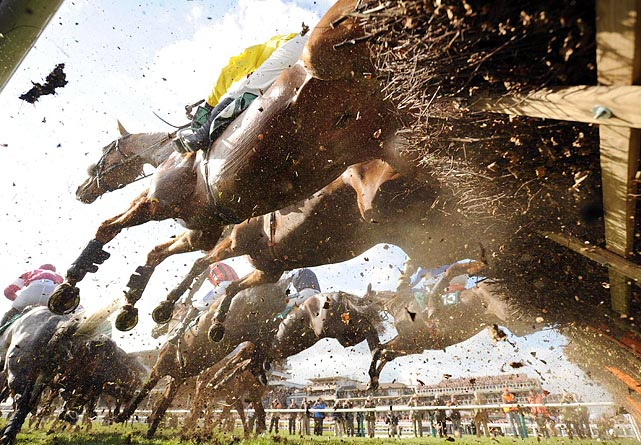 Several steeds hurdle an obstacle during the horse jump race at the Cheltenham Festival in England.