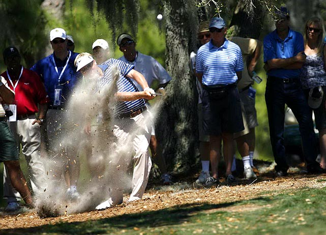 A golfer stirs up a plume of dust while salvaging his ball from the straw during the Transitions Championship in Palm Harbor, Fla.