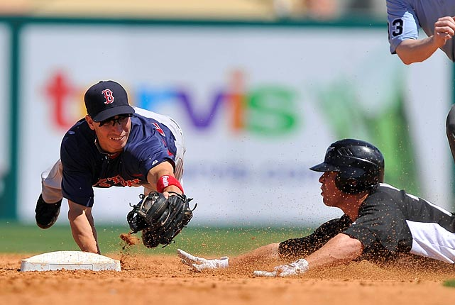 Florida Marlins third baseman Donnie Murphy (right) barely slips beneath a tag from Boston Red Sox third baseman Nate Spears during a spring training game at Roger Dean Stadium.