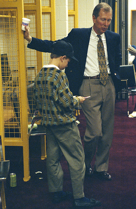 The team was led by Steve Fisher, who took over as the Wolverines coach in 1989 and led the team to that season's national championship. In this photo, Fisher talks with his son Mark in the Michigan locker room.