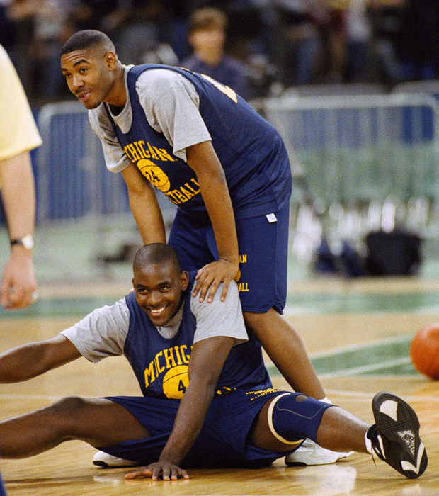 Michigan returned for the 1992-93 season determined to win a national championship. In this photo from an early November practice, Jimmy King lends a hand to Chris Webber as the forward stretches his legs.