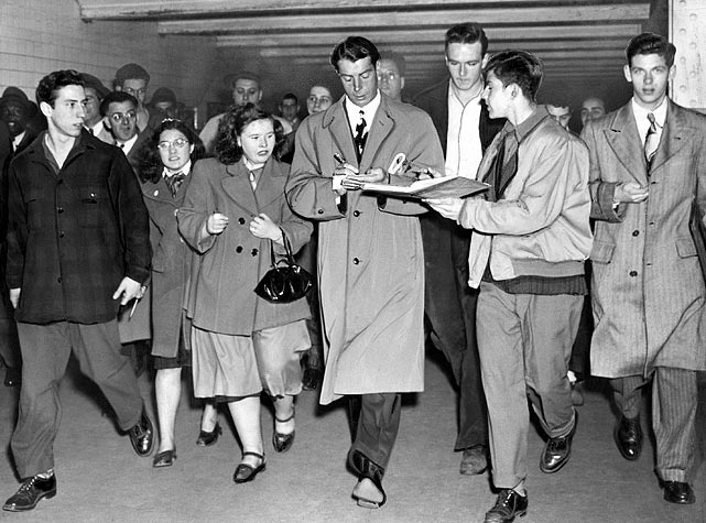 DiMaggio signs autographs for fans who met him at Penn Station in New York City.