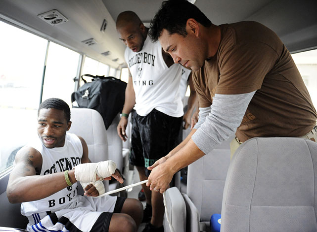 De La Hoya (right) helps tape up Adrien Broner as Seth Mitchell looks on at Area Support Group at Camp Arifjan, Kuwait.