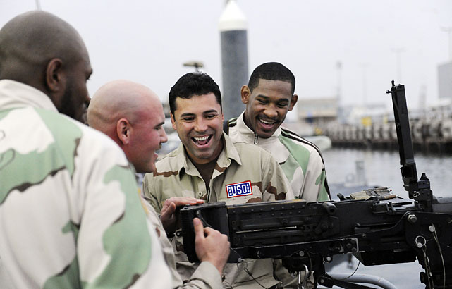 De La Hoya (second from right) is given basic operating instructions on the .50-caliber machine gun aboard a U.S. Navy patrol boat in Kuwait as Danny Jacobs (right) and Seth Mitchell (left) look on.