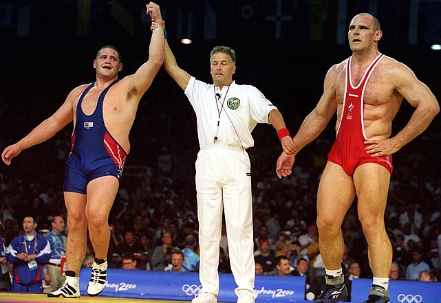An official declares Gardner the winner of the Greco Roman wrestling gold medal in the 130-kilogram division over Alexander Karelin.  With four seconds left in the match, Karelin bowed his head and conceded to Gardner, a heavy underdog going into the match.