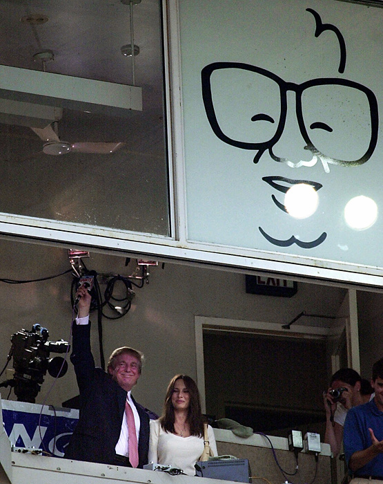 "Trump waves from the press box after singing ""Take Me Out to the Ballgame"" during the seventh-inning stretch of a July 2000 game between the Cubs and White Sox. He was joined by future wife Melania Knauss."