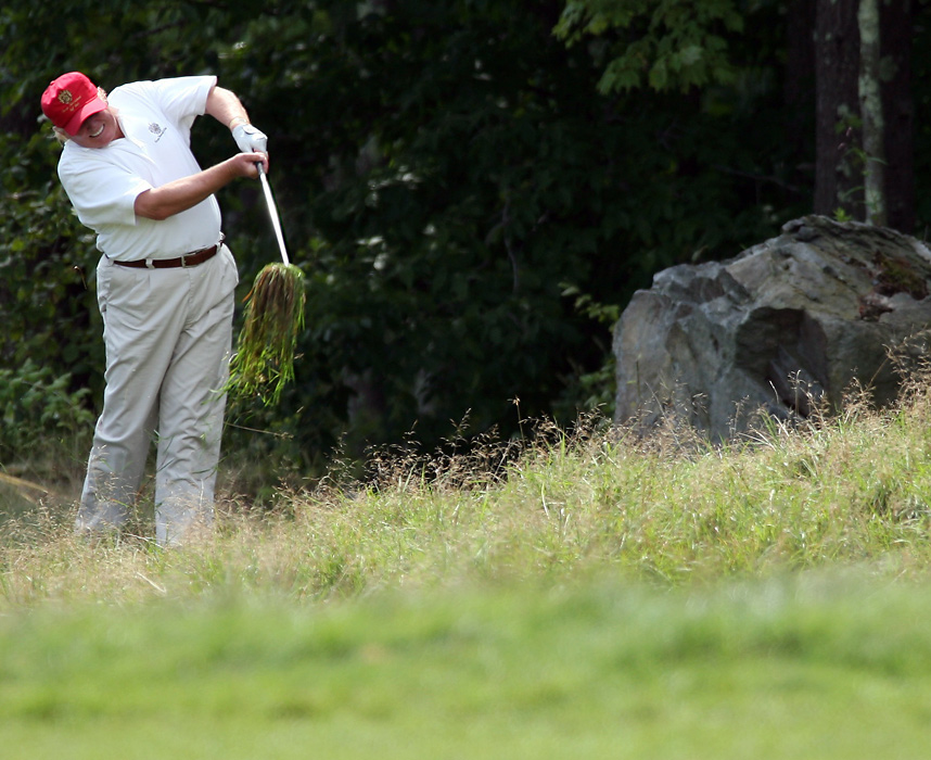 Trump hits a shot from the rough on the ninth hole of the Deutsche Bank Championship Pro-Am golf tournament in August 2008.