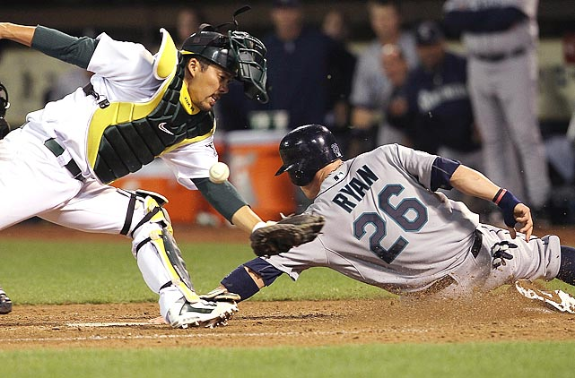 Seattle Mariners shortstop Brendan Ryan slides safely into home as Oakland Athletics catcher Kurt Suzuki is unable to corral the throw.  The Mariners would defeat the A's 6-2 behind a stellar effort from reigning AL Cy Young winner Felix Hernandez.
