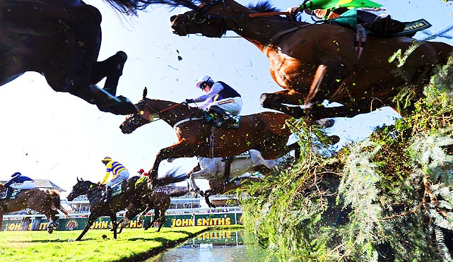 Peter Toole and his horse Fine Parchment bound over the 'Water Jump' during the second day of the Grand National, the famed steeplechase in Liverpool, England.