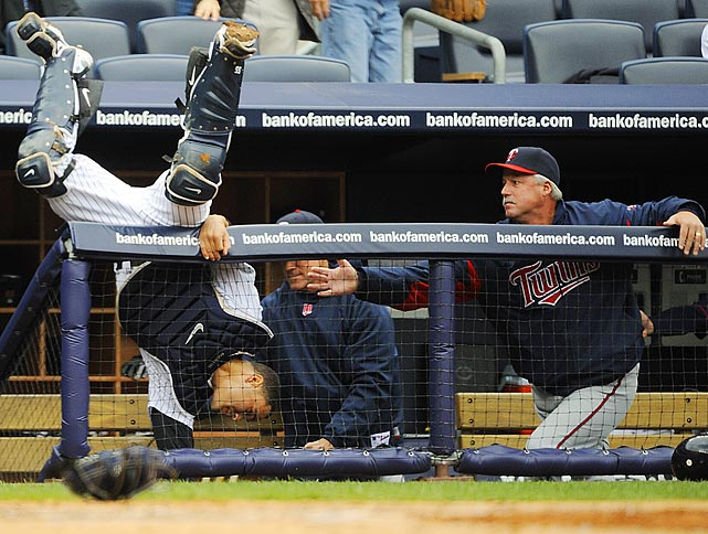 Minnesota Twins pitching coach Rick Anderson attempts to catch Russell Martin as he falls over the dugout railing during the Yankees' 4-3 victory over the Twins.