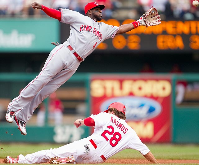 St. Louis Cardinals outfielder Colby Rasmus (bottom) slides safely in to second beneath a leaping Brandon Phillips. Phillips and the Reds would prevail over the Cardinals 5-3 on April 23.