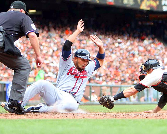 Look ma, no hands!  Atlanta Braves shortstop Alex Gonzalez slips by San Francisco Giants catcher Buster Posey for the third run in the Braves' 5-2 victory over the Giants on April 23.