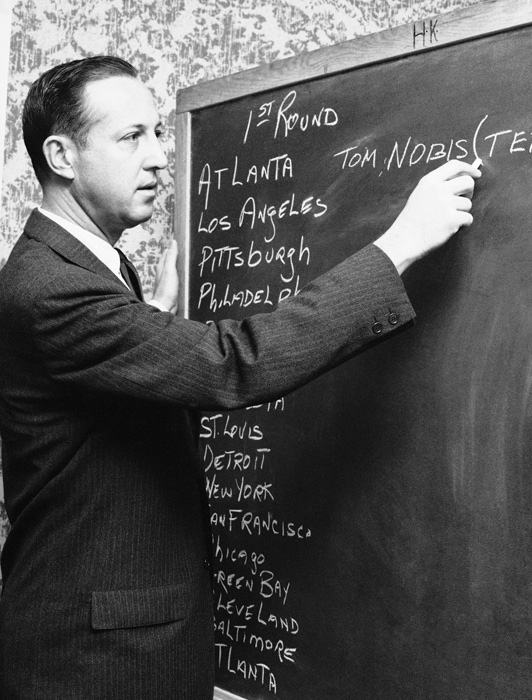 The NFL commissioner writes down the name of Tommy Nobis, the linebacker drafted by the Atlanta Falcons with the first pick. The draft has changed dramatically since its founding in 1936.