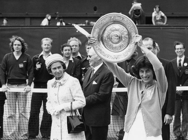 Queen Elizabeth II watches as Virginia Wade shows her women's singles champion trophy to the crowd on the centre court at Wimbledon. Wade has just beaten Betty Stove of the Netherlands in the final.
