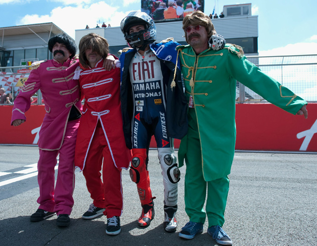The Spanish motorcycle racer celebrates his victory at the MotoGP race in England with fans dressed as the Beatles.